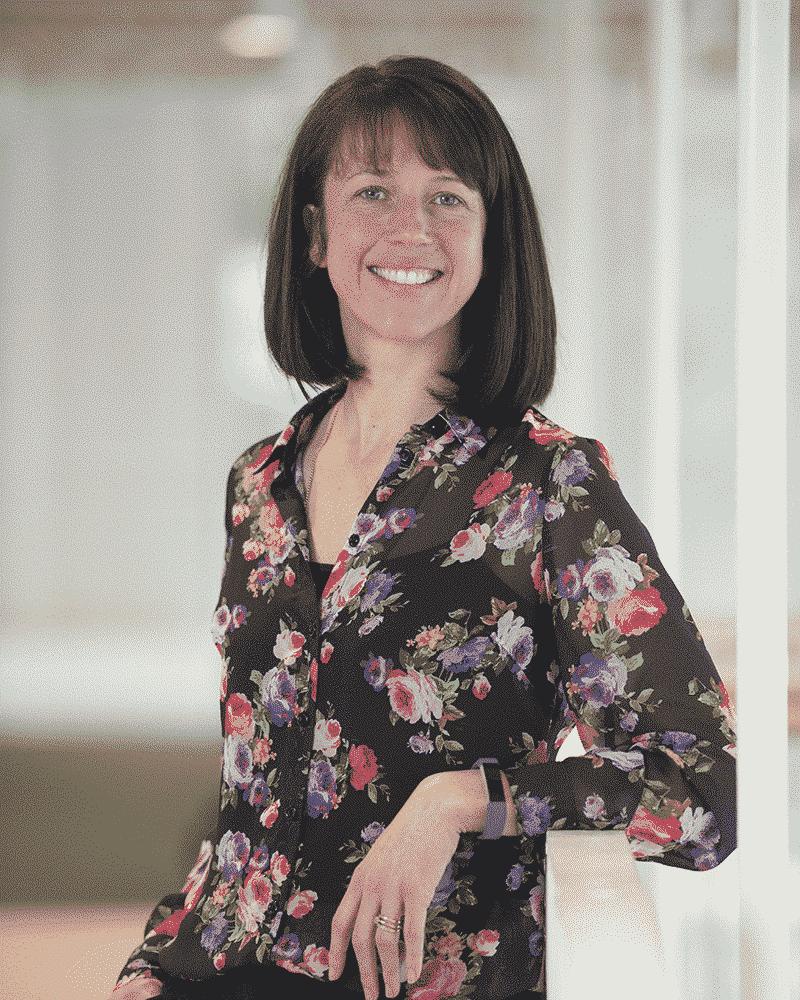 Prof. Saoirse O'Sullivan leaning on a railing, smiling at camera.