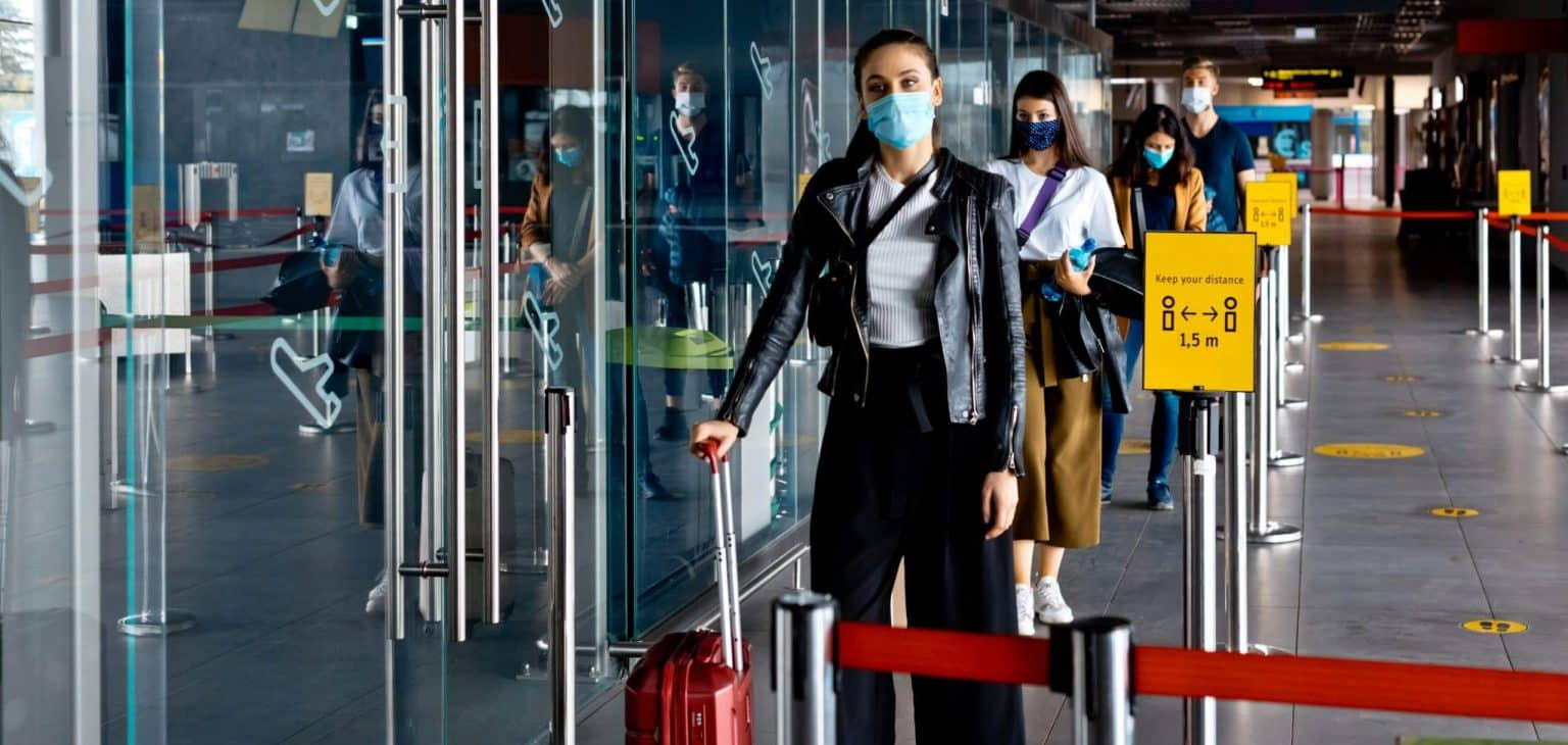 People traveling by airplane during COVID 19, wearing N95 face masks, carrying luggage and waiting in line at airport terminal, keeping distance.