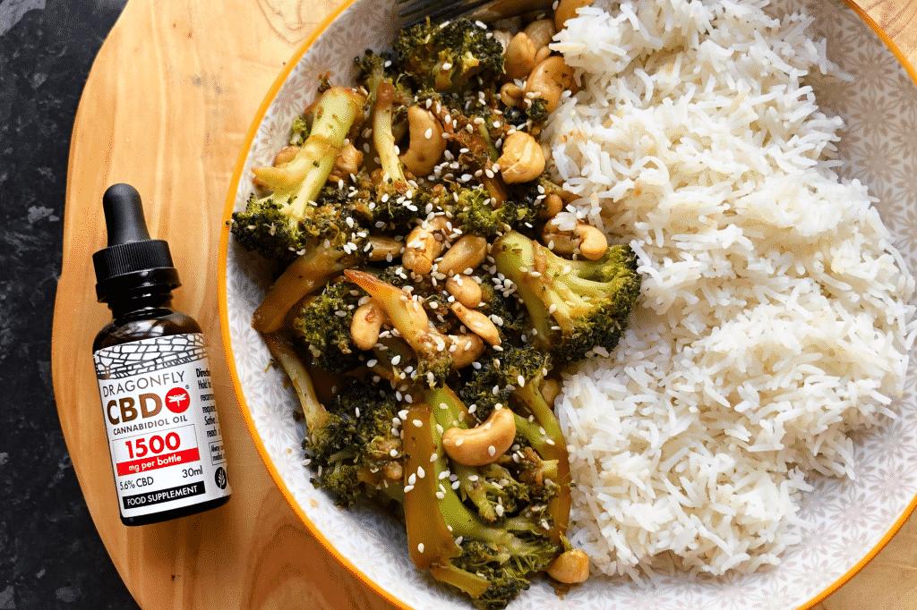 Cashew and broccoli vegan stir fry next to a bottle of dragonfly cbd