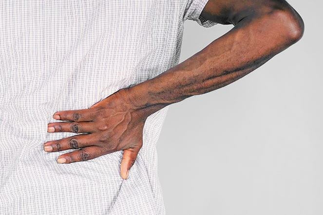 African man with joint pain at lower back